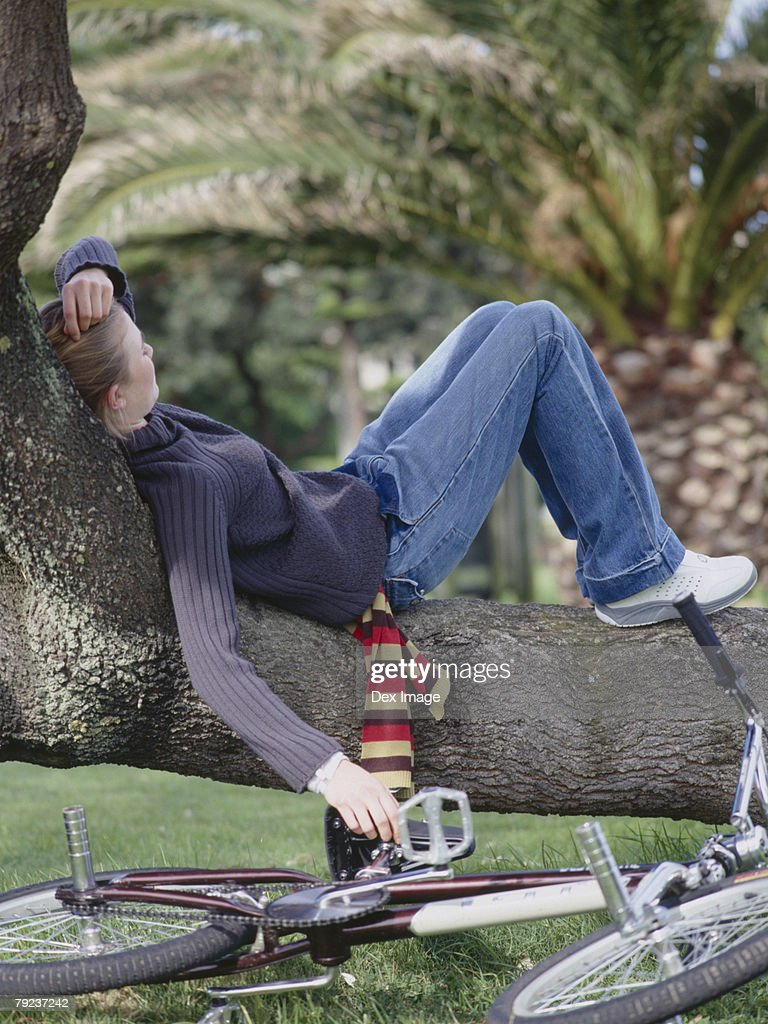Young woman lying on bent tree trunk : Stock Photo
