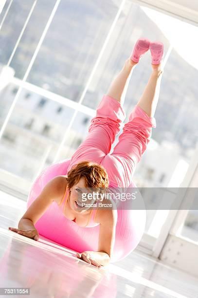 Young woman lying on big pink balloon
