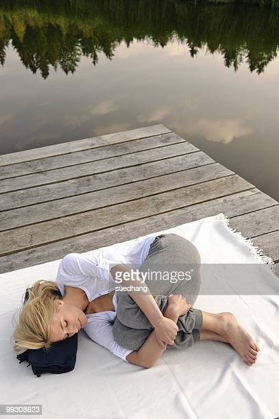 Young woman lying on blanket by lake