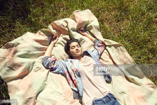 Young woman lying on blanket listening music with headphones