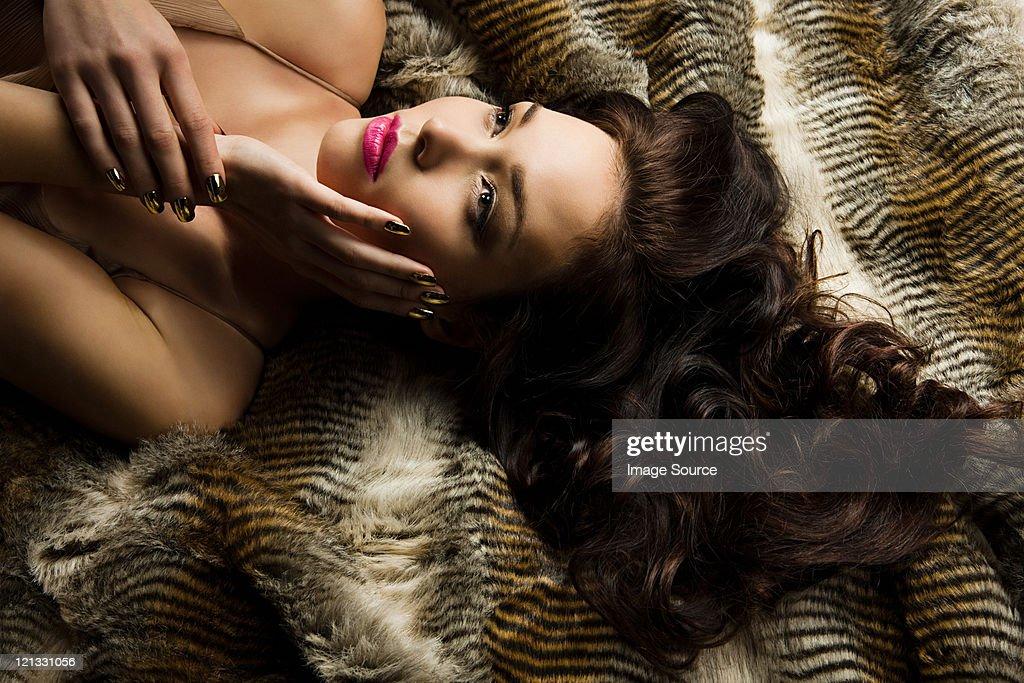 Young woman lying on blanket, portrait : Stock Photo