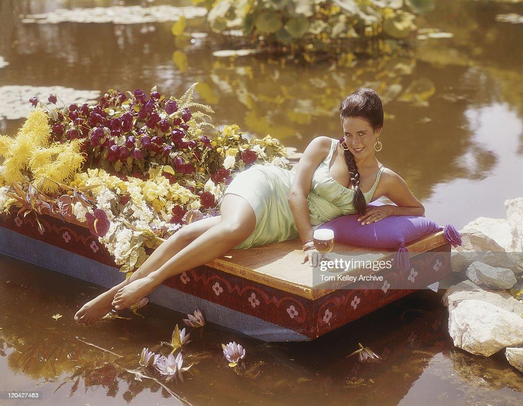 Jeune femme allongée sur un bateau avec Verre à bière, à côté de fleurs