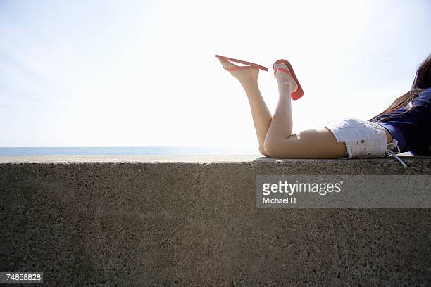 Young woman lying on breakwater, side view