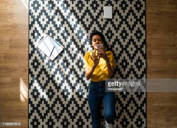 young woman lying on carpet at home using smartphone - lying down 個照片及圖片檔