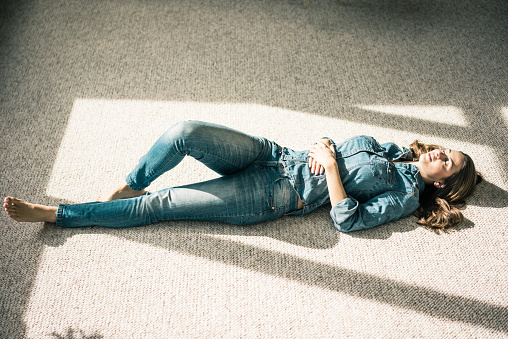 Young woman lying on carpet in the living room enjoying sunlight - gettyimageskorea