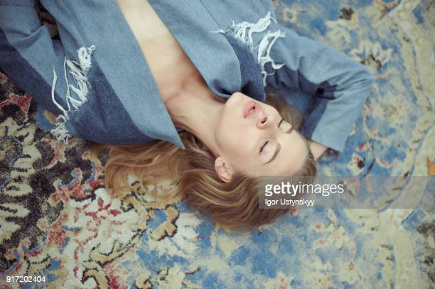 Young woman lying on carpet with closed eyes