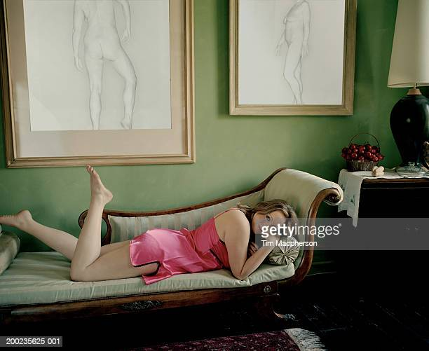 young woman lying on chaise longue, smiling, portrait - dessin erotique photos et images de collection