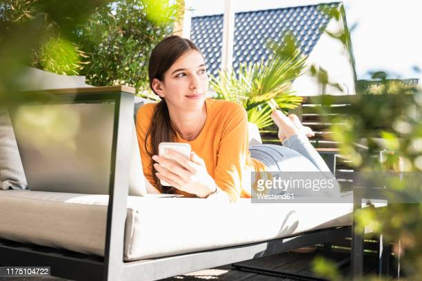 young woman lying on couch on terrace using cell phone and laptop - 18 19 jahre stock-fotos und bilder
