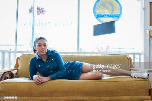 young woman lying on couch - mini dress stock pictures, royalty-free photos & images