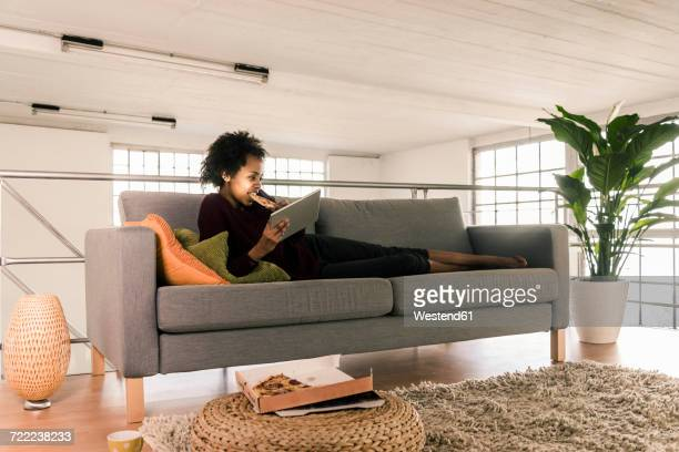 Young woman lying on couch using tablet and eating pizza