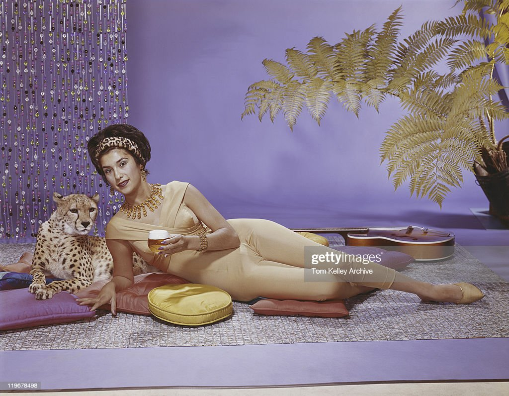 Young woman lying on cushion with leopard : Stock Photo