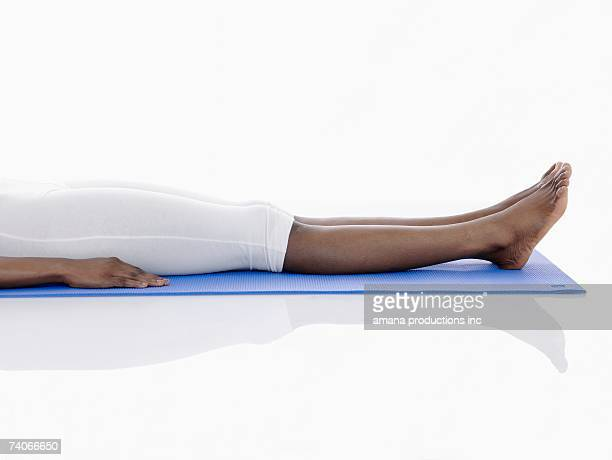 Young woman lying on exercise mat (low section)