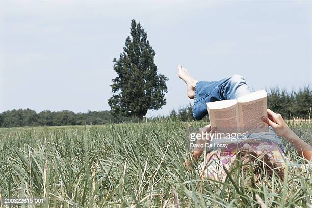 Young woman lying on field, reading book