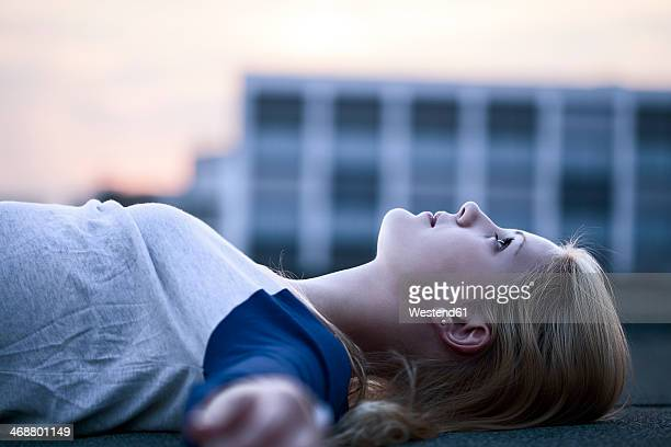 Young woman lying on flat roof