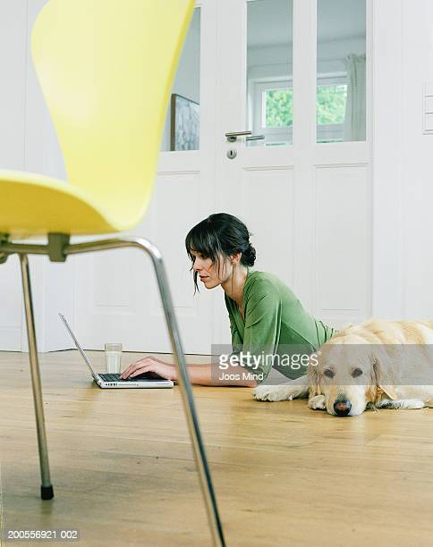 young woman lying on floor beside dog in living room, using laptop - ミュンスター市 ストックフォトと画像