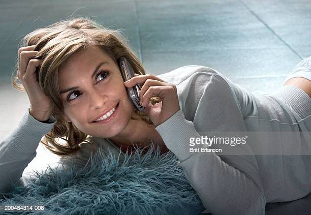 Young woman lying on floor, using mobile phone, smiling