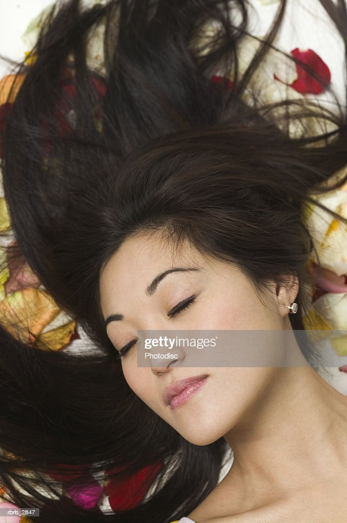 Young woman lying on flower petals : Foto de stock