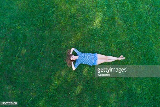 young woman lying on grass, daydreaming - lying down fotografías e imágenes de stock