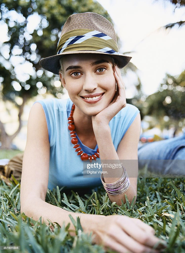Young Woman Lying on Grass in a Park Wearing a Trilby Hat : Stock Photo