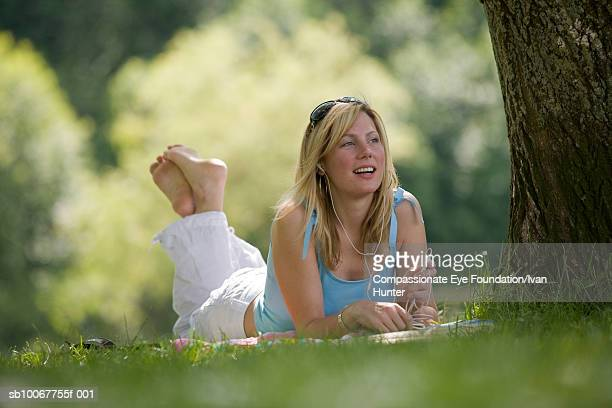 Young woman lying on grass in park, listening to music