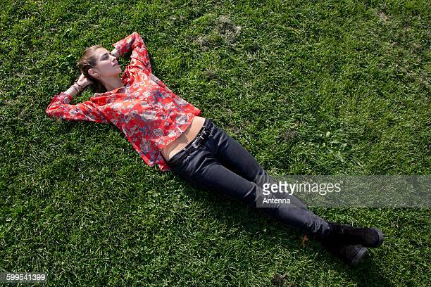 young woman lying on grass in park - lying down stock pictures, royalty-free photos & images