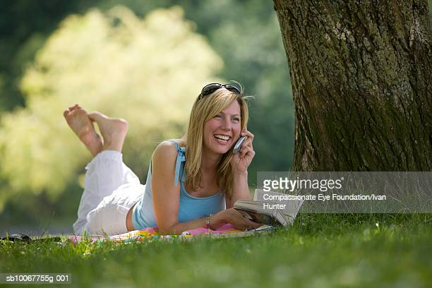 Young woman lying on grass in park, talking on cell phone