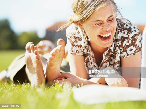 Young woman lying on grass laughing, ground view