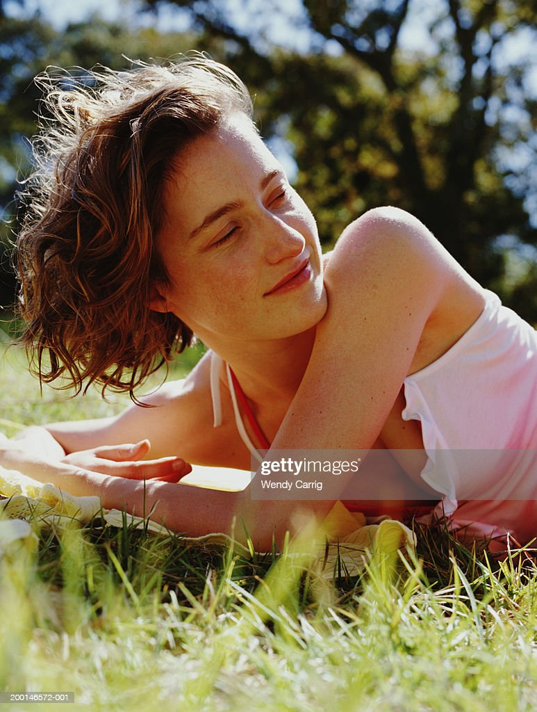 Young woman lying on grass, looking over shoulder, ground view : Stock Photo