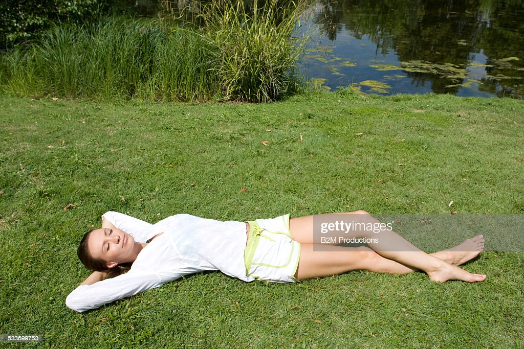 Young woman lying on grass : Foto stock