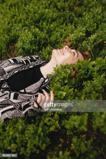 young woman lying on grass - 腹ばい ストックフォトと画像