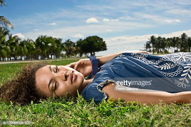 Young woman lying on grass, portrait, close-up
