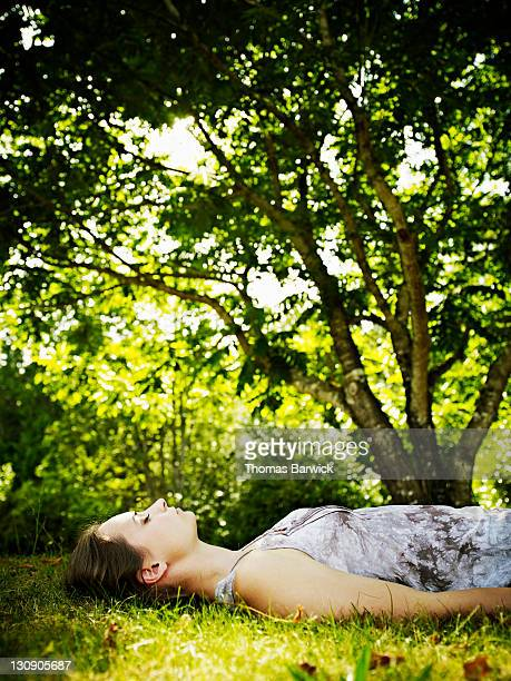 Young woman lying on grass under tree eyes closed