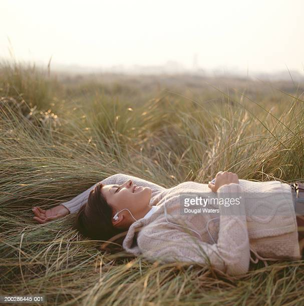 Young woman lying on grass wearing earphones, eyes closed, side view