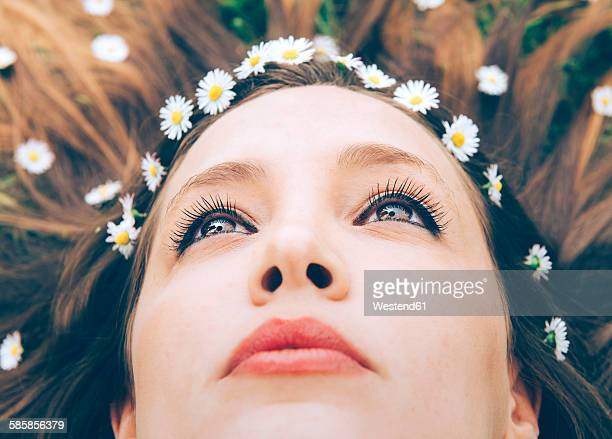 Young woman lying on grass with daisies in the hair, close-up