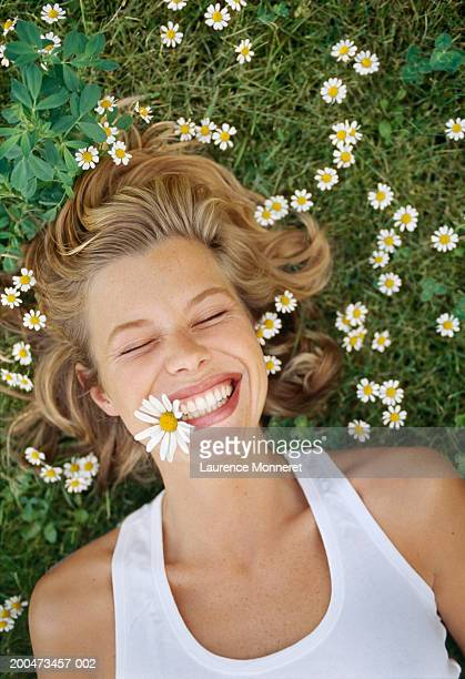 young woman lying on grass, with daisy in mouth, smiling - lying down stock pictures, royalty-free photos & images