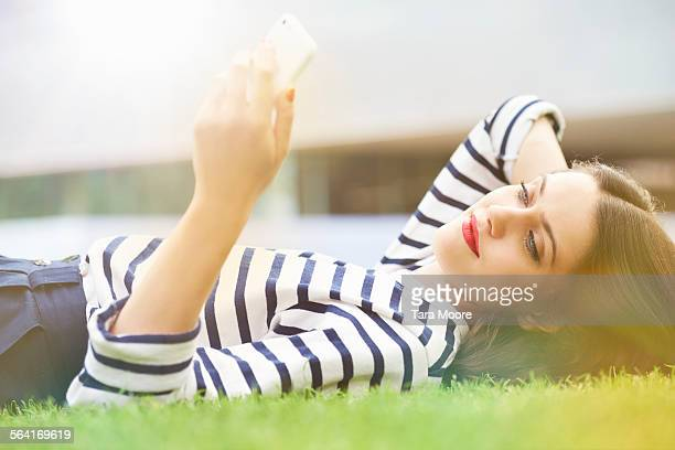 young woman lying on grass with mobile phone - manches longues photos et images de collection