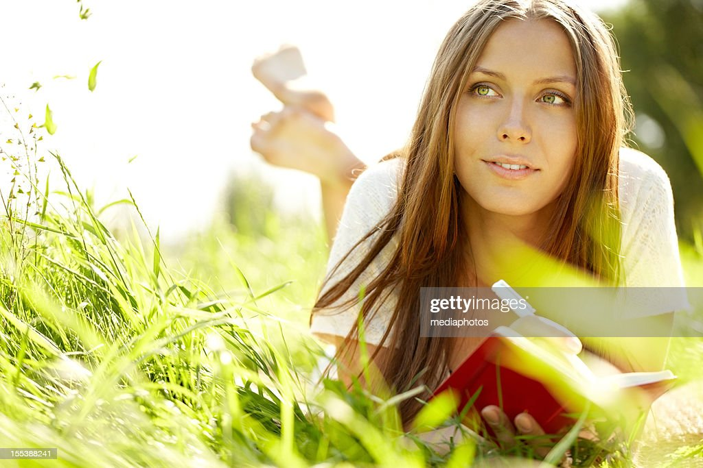 Young woman lying on grass with notepad and pen : Stock Photo