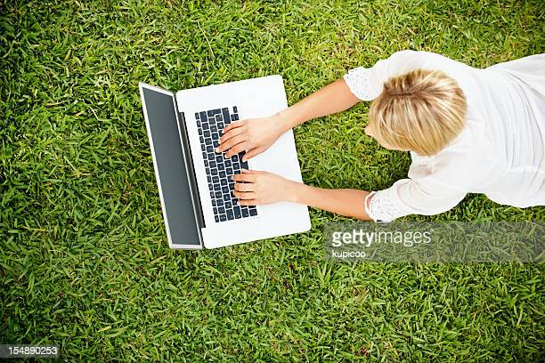 Young woman lying on green grass and using laptop