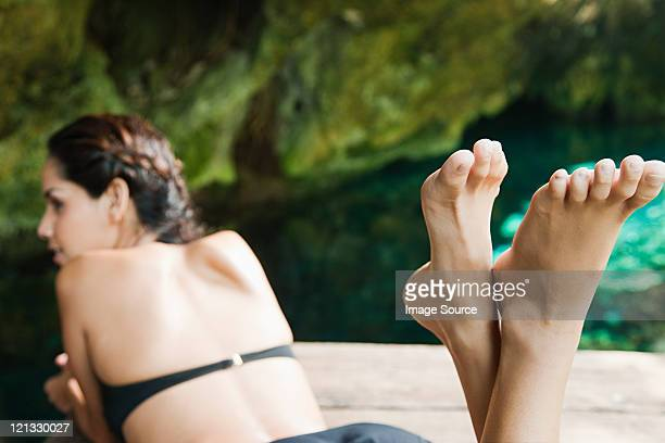 young woman lying on jetty, grande cenote, quintana roo, tulum, mexico - woman lying on stomach with feet up stock photos and pictures
