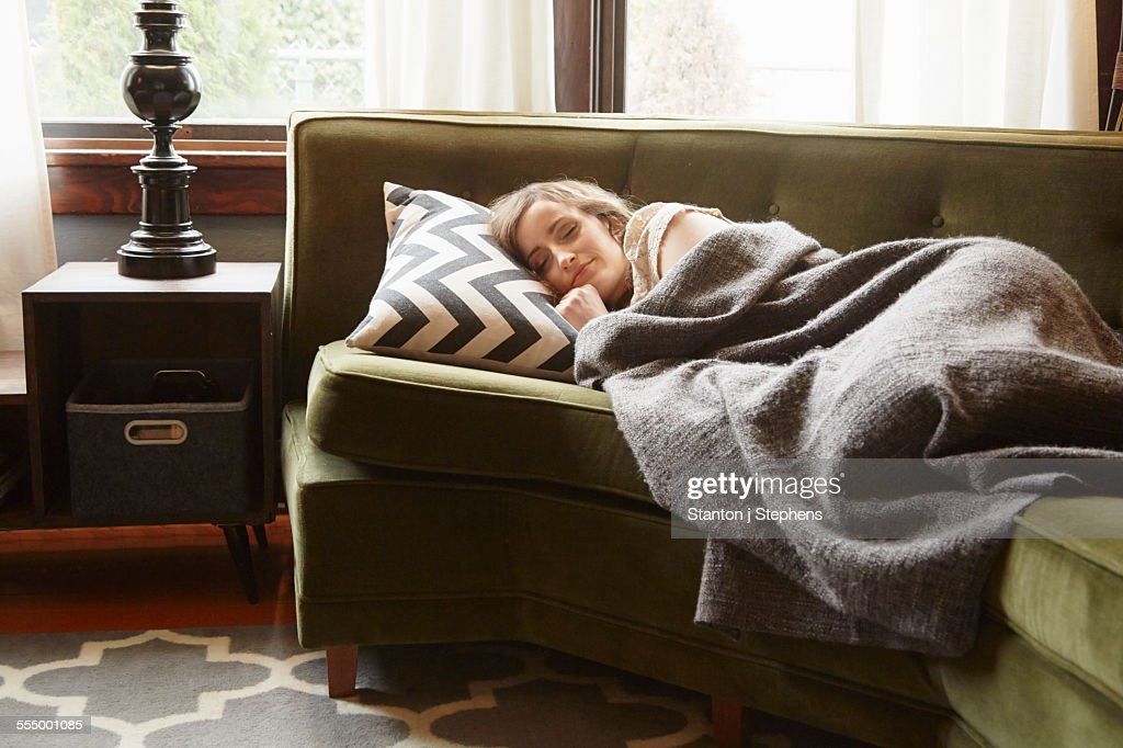 Young woman lying on living room sofa wrapped in blanket : Stock Photo