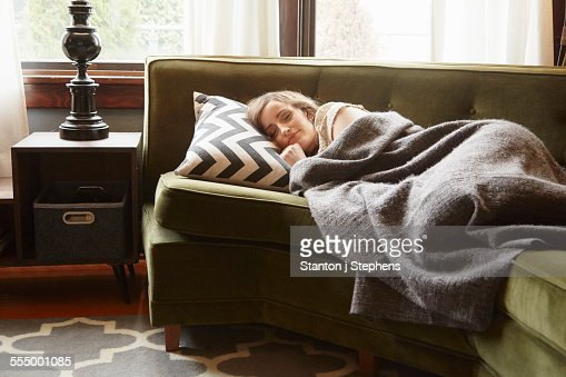Young Woman Lying On Living Room Sofa Wrapped In Blanket High Res Stock Photo Getty Images