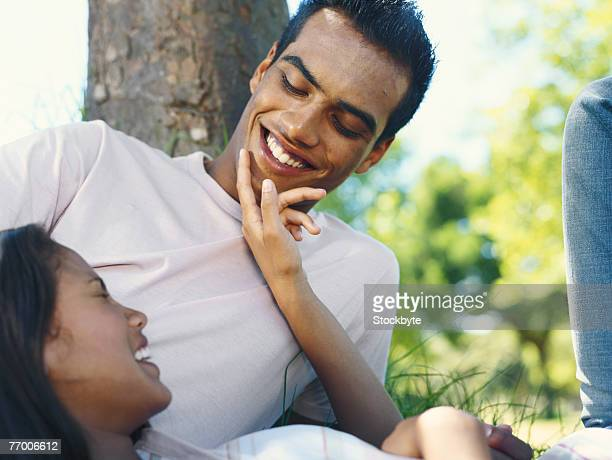 Young woman lying on man's lap, smiling