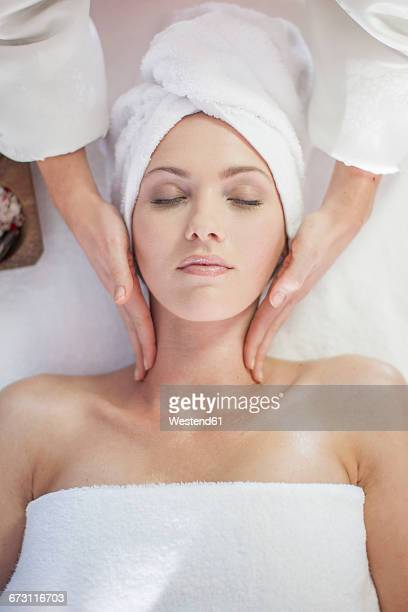young woman lying on massage table receiving beauty treatment - massage parlour stock photos and pictures