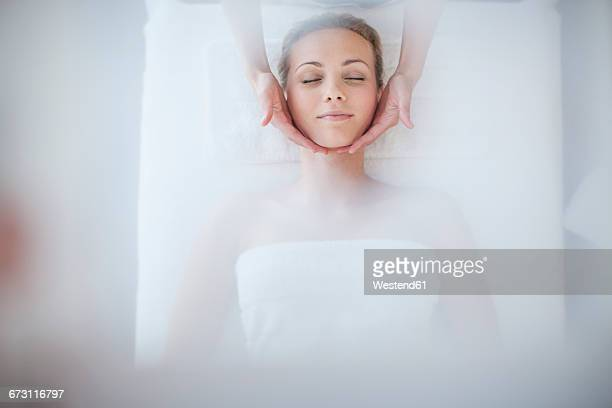 young woman lying on massage table receiving beauty treatment - massage rooms photos et images de collection