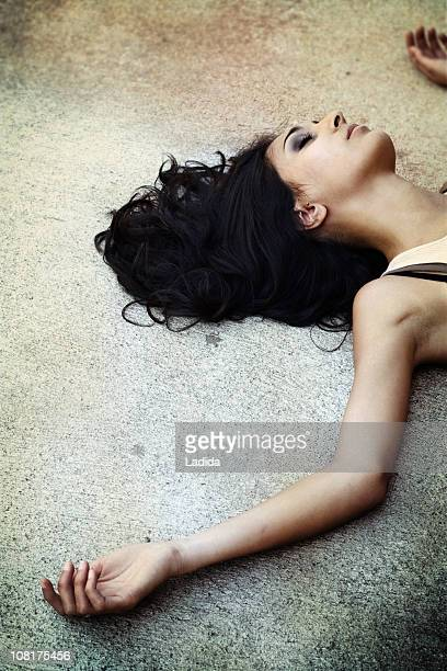 young woman lying on pavement - dead body stockfoto's en -beelden