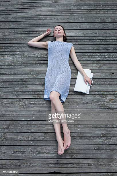 young woman lying on pier - lying down ストックフォトと画像