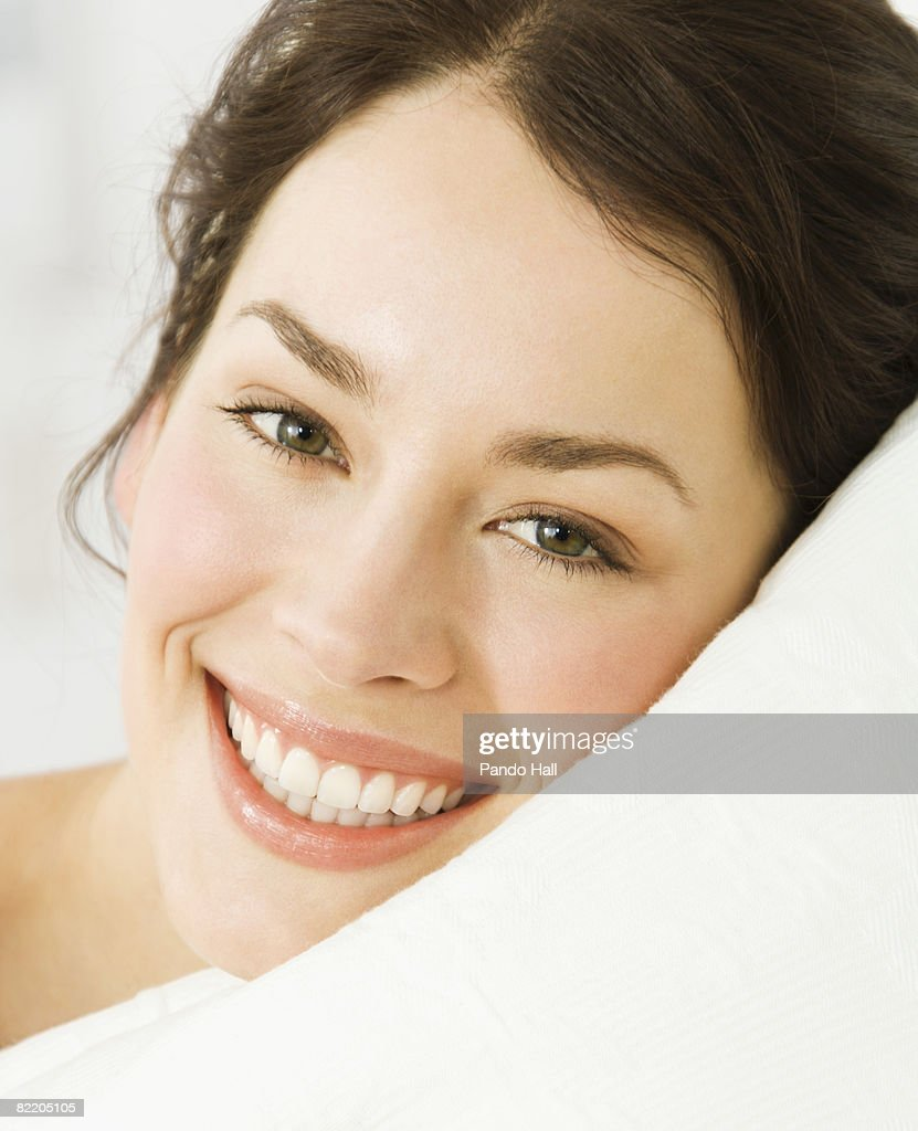 Young woman lying on pillow, smiling : Stock Photo