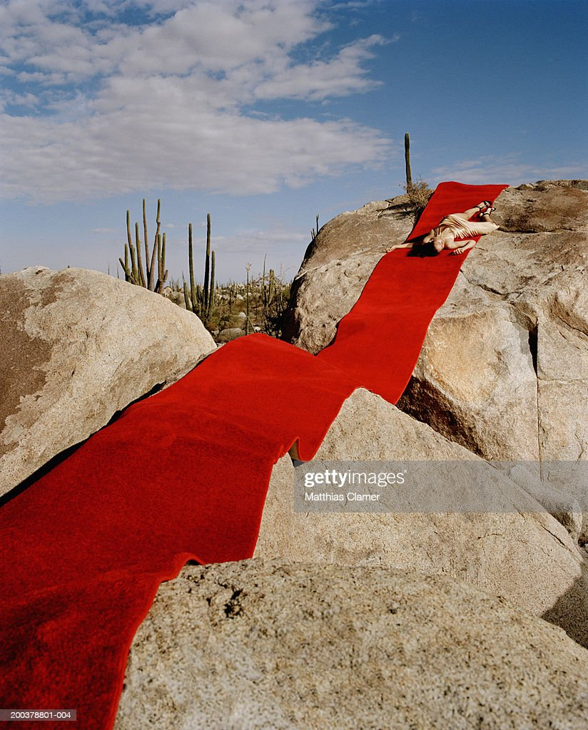 young woman lying on red carpet laid on rocks ストックフォト getty