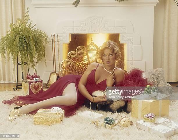 jeune femme allongée sur le tapis avec un cadeau devant la cheminée - erotisme vintage photos et images de collection