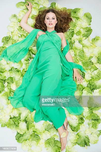 Young woman lying on salad